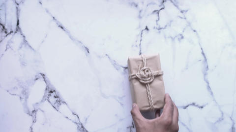 Top view of man hand placing gift box on tiles background, Live Action