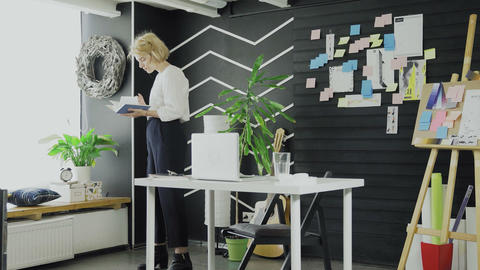 Young Woman is Reading Book while walk in office Live Action
