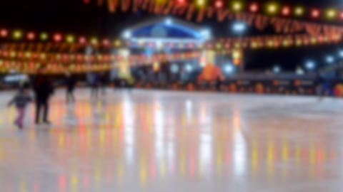 People ride on an ice rink with luminous glowing yellow-red garland lamp Live Action
