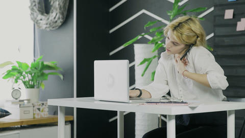 Young businesswoman is talking on her smartphone while working on notebook Live Action