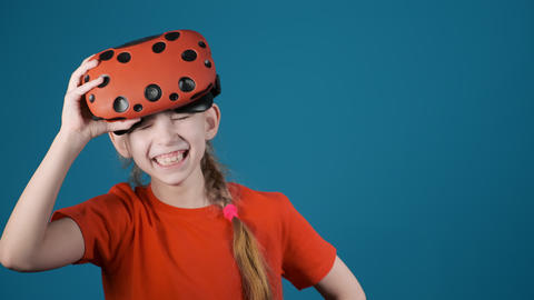 little girl laughs holding virtual reality glasses on head Live Action
