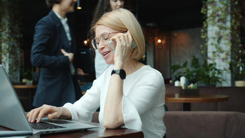 Mature business woman making mobile call and working with laptop in cafe alone Live Action
