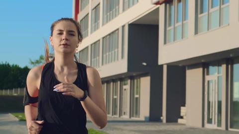 girl in black tracksuit start runs past modern building on street Live Action
