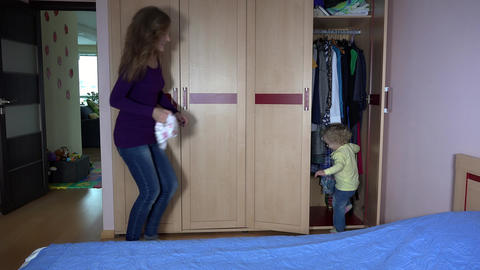 mother catching daughter wants to change diapers. girl hiding in closet. 4K Live Action