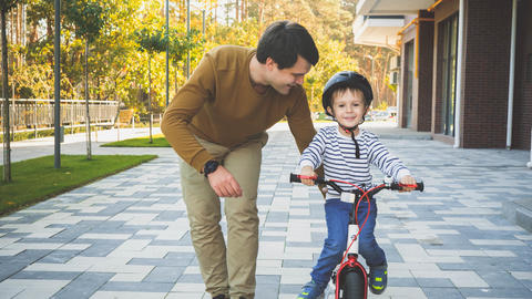 Toned image of happy smiling little boy riding his first bicycle with father Photo