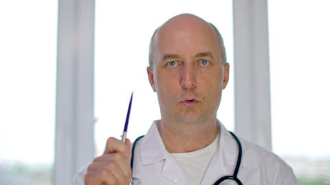 Serious male doctor in white coat explaining diagnosis and looking at camera GIF