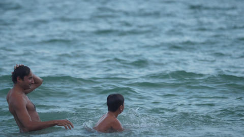 A boy jumps into the water with his father's shoulders Slow motion video Live Action