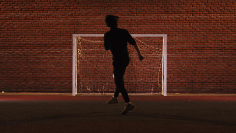 Young man playing football on the playground at night - kicking ball in gates Live Action