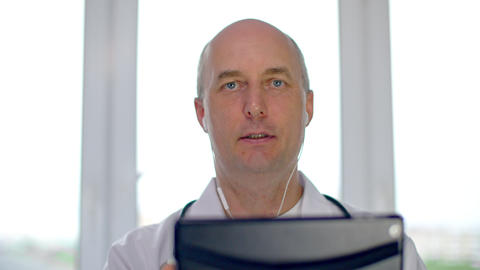 Serious doctor in earphones holding digital tablet and talking during online Live Action