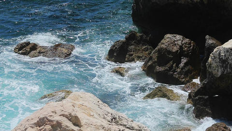 Waves break about the rocky coast of the azure coast, splashes, clear water Live Action