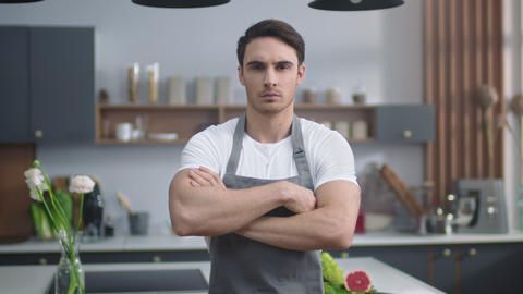 Serious chef male looking camera at home kitchen. Man crossing hands indoors Live Action
