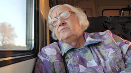 Old woman looks through the window in a train Acción en vivo