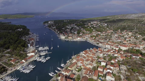 Aerial view of port in Milna, Croatia, drone view point, a full rainbow on the Live Action