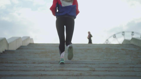 Back view of woman in sports clothes running stairs. Elegant woman run stairs in Live Action