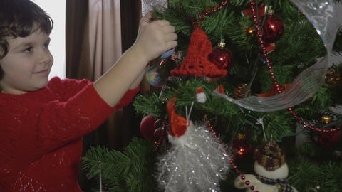 Young beautiful girl decorating the Christmas tree - 4k Footage