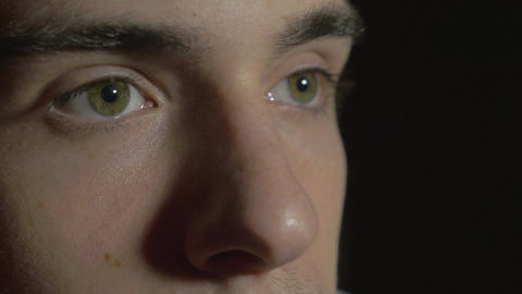 4k UHD - Close-up of a young man eyes in the dark watching TV Footage