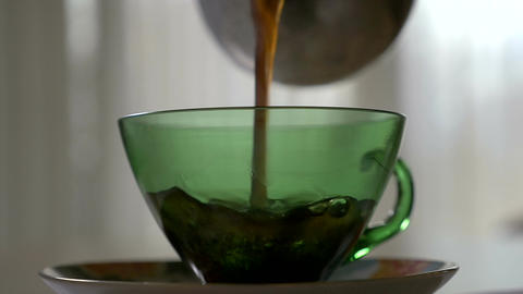 Pouring hot coffee in a transparent cup in the morning in slowmotion Footage