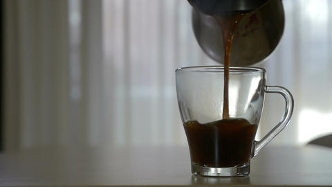 Pouring hot coffee in a transparent mug in the morning in slow motion Footage