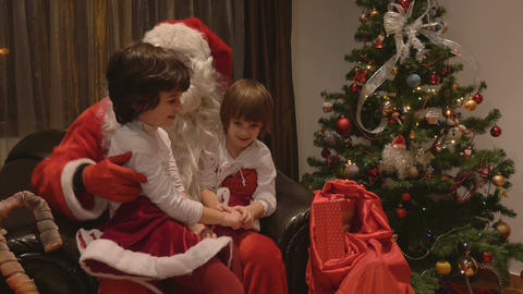 Young beautiful twin girls sitting in Santa Claus lap on Christmas day - 4k Footage