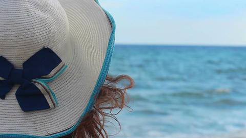 Close-up of woman in hat relaxing on sunny beach at seaside, enjoying seascape Footage