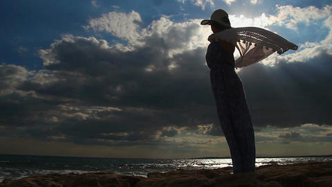 Timelapse of strong woman alone on seashore, female silhouette, dark cloudy sky Footage