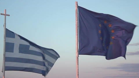 Flags of Greece and EU waving in wind against blue sky background, debt crisis Footage