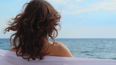 Closeup back view of tender feminine woman relaxing on beach at seaside, summer Live Action