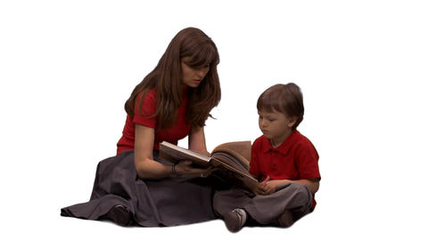 A little boy listening to his mother reading a book, alpha channel Footage