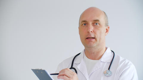 Professional male doctor holding clipboard with pen and talking about diagnosis GIF