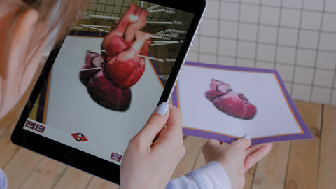 Woman using tablet device with augmented reality app - 3d model of human heart Live Action