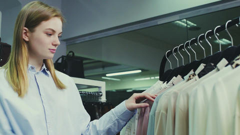 Young pretty girl in boutique selecting clothes to buy Live Action