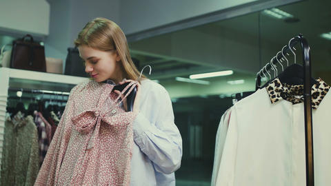 Young woman tries on clothes at clothes store Live Action