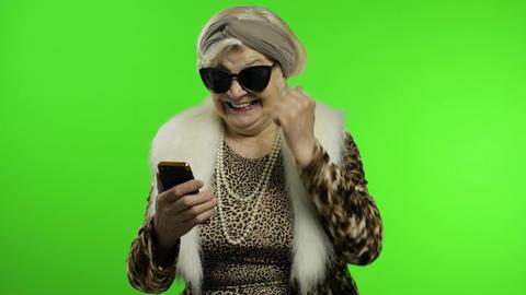 Elderly stylish trendy caucasian grandmother woman using smartphone. Chroma key Live Action