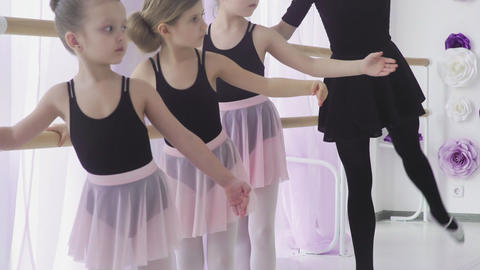 Little girls are having classical ballet lesson learning leg movements with Live Action