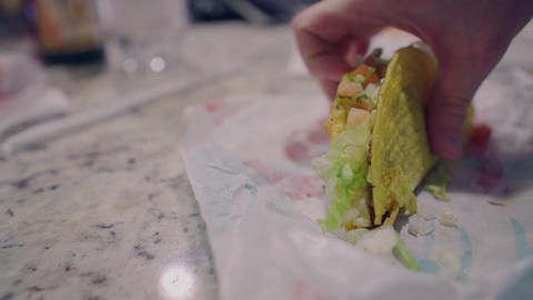 Man eating fast food taco at home, mexican cuisine dinner Live Action
