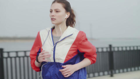 Sporty woman running along the embankment. Girl sport fitness model in sporty Live Action