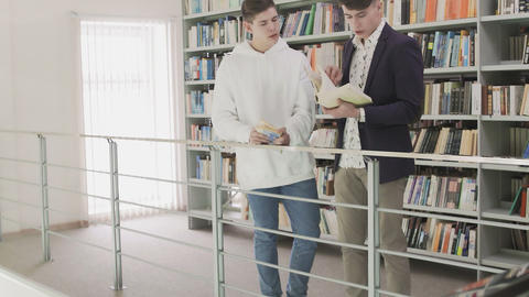 Two young Student Searching Information in Book in Library Live Action