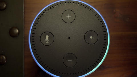 Amazon Alexa Echo Dot from above, activating and responding to voice command Live Action