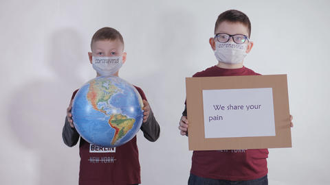 Boy holds a globe, a model of the planet Earth. Child is holding a sign with the inscription: WE Live Action