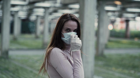 Girl in protective mask and rubber gloves depicts horror and fear Live Action