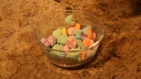 Valentine candy hearts dropping into bowl P HD 6342 Footage