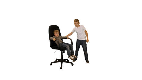 Happy boy whirling his little brother on the chair, alpha channel Footage
