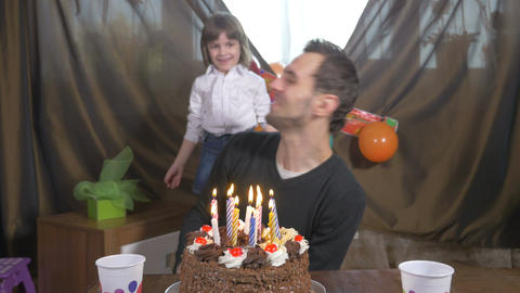 Young handsome man blowing candles on a birthday cake with his daughter at a sur Footage