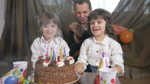 4k - Young beautiful girl blowing candles on a birthday cake with her father and Footage