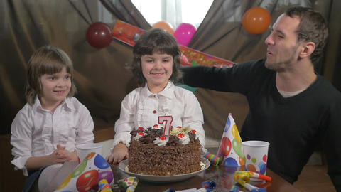 Young beautiful girl blowing candles on a birthday cake with her father and twin Footage