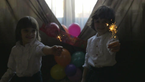 Young beautiful twin sisters playing with fireworks at a birthday party, slow mo Footage