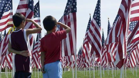 Boys saluting American flags waving in wind Footage