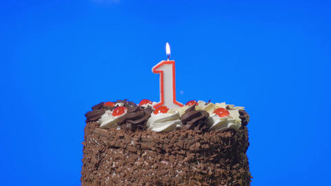 4k - Blowing out number one birthday candle on a delicious chocolate cake, blue  Footage