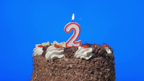 4k - Blowing out number two birthday candle on a delicious chocolate cake, blue  Footage