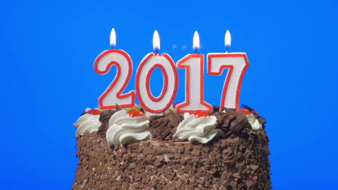 Blowing out new year 2017 candles on a delicious chocolate cake, blue screen Footage